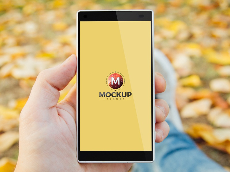 Free man in park holding smartphone psd mockup