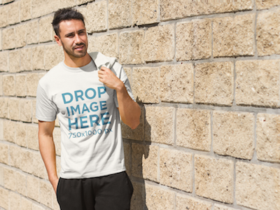 Young Man Standing Next to a Brick Wall T-Shirt Mockup