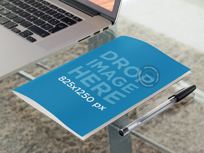 Bifold Brochure Mockup Lying Next to a Laptop in an Office