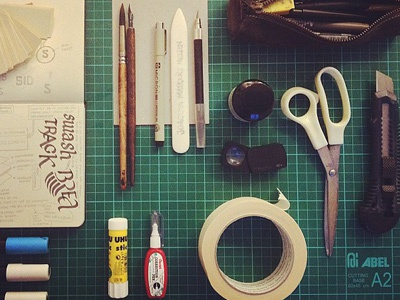 Tools tools workspace materials toolkit scissors pencils pens moleskine markers posca ink paper tape glue equipment illustration ready creativity creative book ruler grid graphic design tools of the trade cut board spray can top view