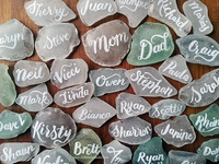 Hand lettered names onto sea glass for wedding place cards