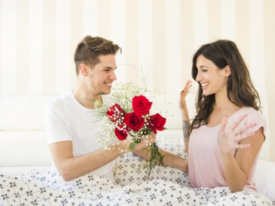 man giving flowers woman bed 23 2147744419