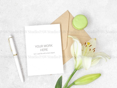 Flat lay invitation card with craft envelope, lily and macarons