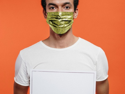Man in a Face Mask Holding the Poster Free PSD Mockup mockup psd mock-up free psd free download freebie riot psd protest poster mockup man male free mockup facemask face mask