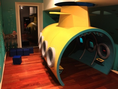 "CCV Lagos Exhibit ""Submarine"" submarine yellow blue window tubes pipes hull tower periscope sceens fiberglass kids playground cubic cube stool exhibit interactive"
