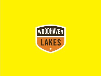 Woodhaven Lakes Badge campground cabin yellow thick star orange brown crest acorn campfire badge campaign camping